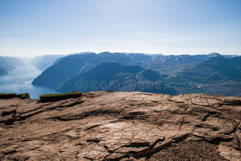 Cliff Preikestolen in Norway. Orange, cracked rocks. Beautiful landscape from a rock shelf stock images