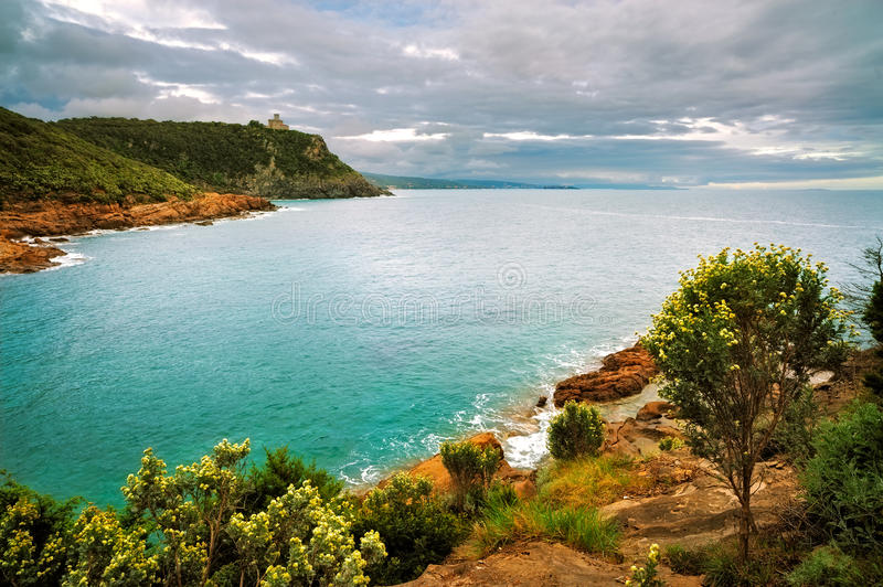 Cliff rock and sea on sunset. Leghorn coast, Tuscany riviera, It. Cliff rock and building on the sea on sunset. Leghorn coast, Tuscany riviera, Italy, Europe stock image