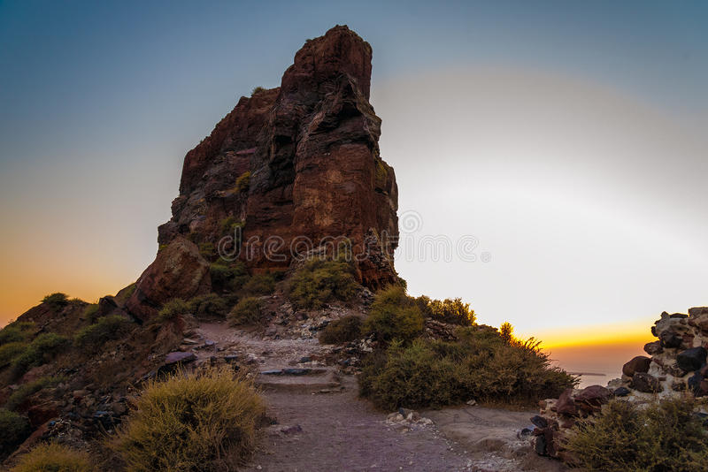 Cliff Scaros durante puesta del sol en la ciudad de Imerovigli en la isla de Santorini fotografía de archivo libre de regalías