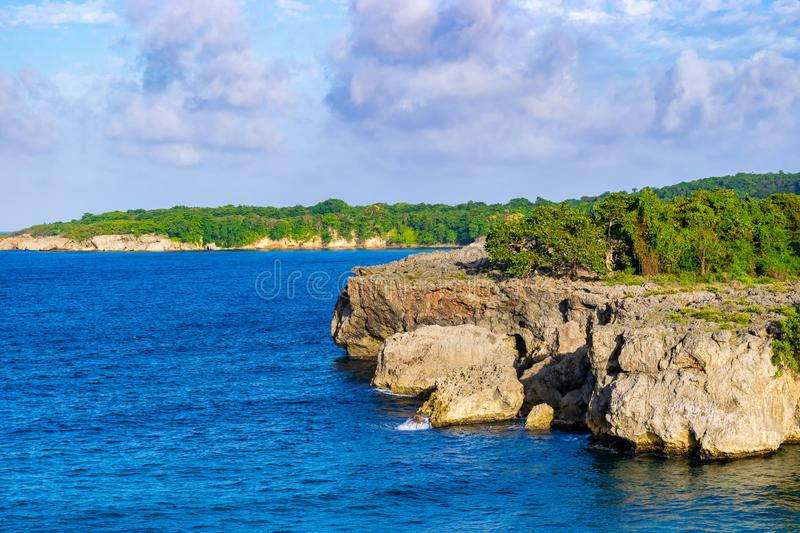 Cliff side/cliffside coastline view on tropical Caribbean island ocean. royalty free stock image