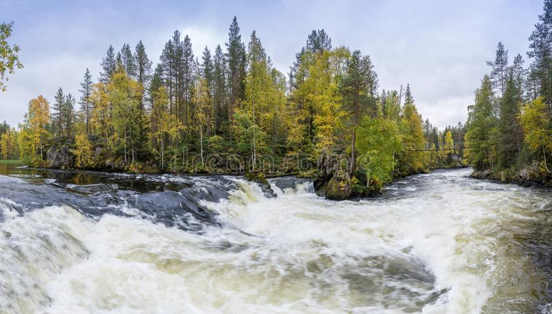 Cliff, stone wall, forest, waterfall and wild river panoramic view in autumn. Fall colors - ruska time in Myllykoski. stock images