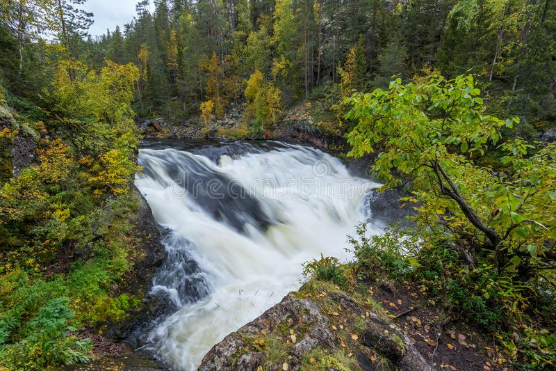 Cliff, stone wall, forest, waterfall and wild river view in autumn. Fall colors - ruska time in Myllykoski. One part of Karhunkierros Trail. Oulanka National royalty free stock image