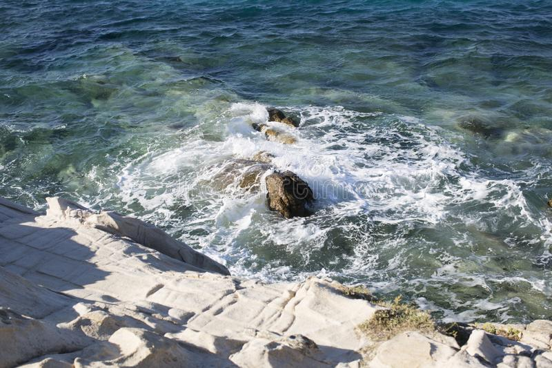 Cliff, stone washed by waves, sea on background. Rocky beach of sea, clear, transparent water near big stone, rock. Nature royalty free stock photo