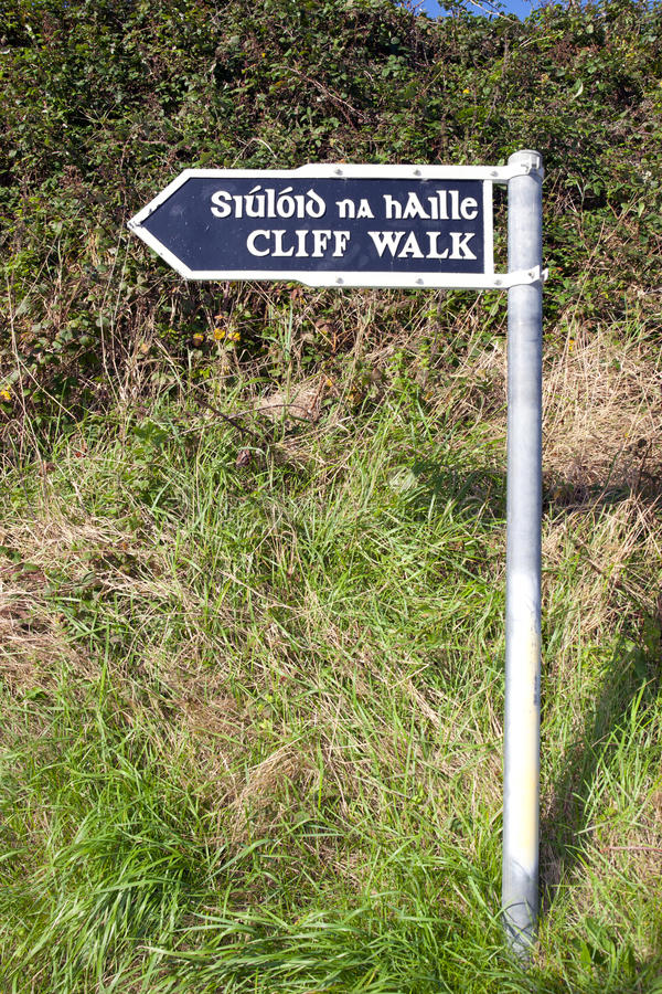 Cliff walk sign in Ballybunion. Cliff walk sign beside the cliffs in Ballybunion county Kerry Ireland in English and Gaelic royalty free stock photo