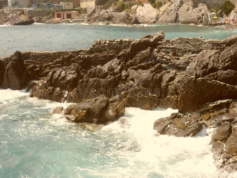 The cliff and the waves crashing on it in the seas of Genoa royalty free stock photo