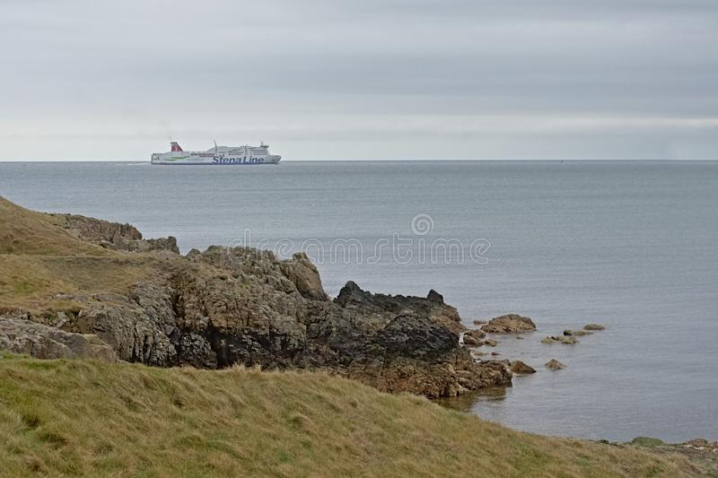 Cliffs along rock coast of howth , ireland, with foggy ferry boat in the distance royalty free stock photos