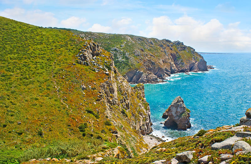 The cliffs of Cape Roca. The picturesque coast of Cape Roca with rocky cliffs, covered with hottentot-figs and huge boulders at the shore, Sintra, Portugal royalty free stock image