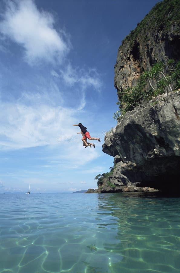 cliffs couple jumping sea στοκ εικόνα