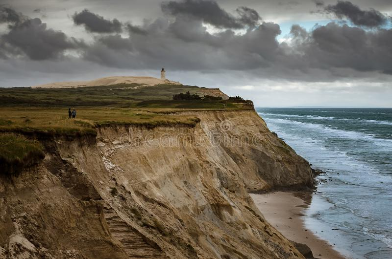 Cliffs in Lonstrup, Rubjerg Knude lighthouse on a dune in the background, north Jutland, Denmark. Cliffs in Lonstrup, Rubjerg Knude Fyr lighthouse on a dune in stock photos