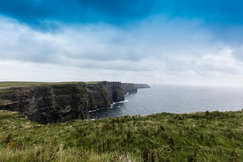The cliffs of Moher. Cliffs of Moher in Ireland in a cloudy day, atlantic, ocean, beach, beautiful, big, blue, clare, coast, coastal, coastline, countryside royalty free stock image