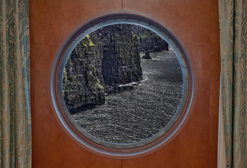 Cliffs of Moher Seen Through Porthole. The Cliffs of Moher in Ireland Seen Through Porthole of a Ship stock photo