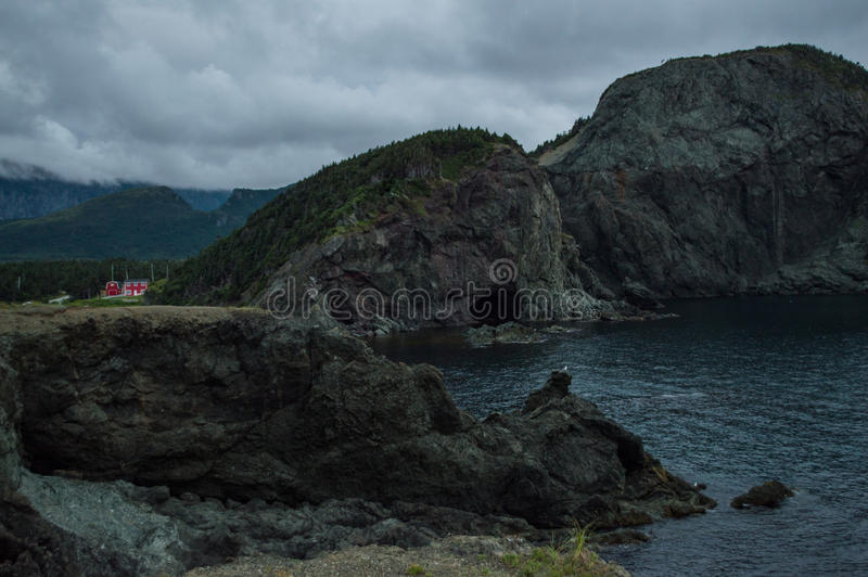 Cliffs and Red House along a Rugged Coastline at Lark Harbor in Newfoundland. Canada royalty free stock photo