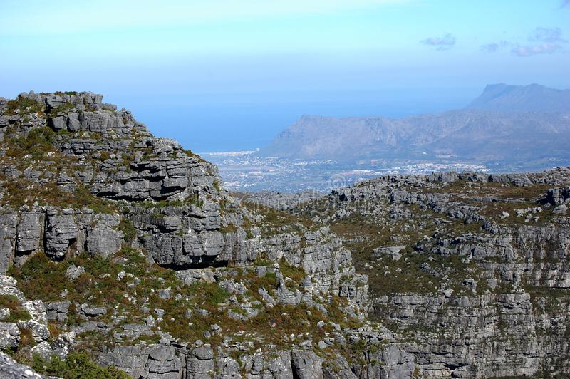 Cliffs and rocks on top of Table Mountain in South Africa. With blue sky and the ocean royalty free stock photography