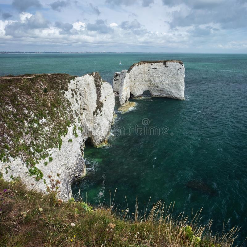 Cliffs on the sea coast. And a sailboat. August - 2019. Old Harry Rocks, England stock photos