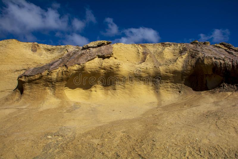 Cliffs shaped by lava on coastal rock. Cliffs shaped by the lava on a coastal rock royalty free stock image