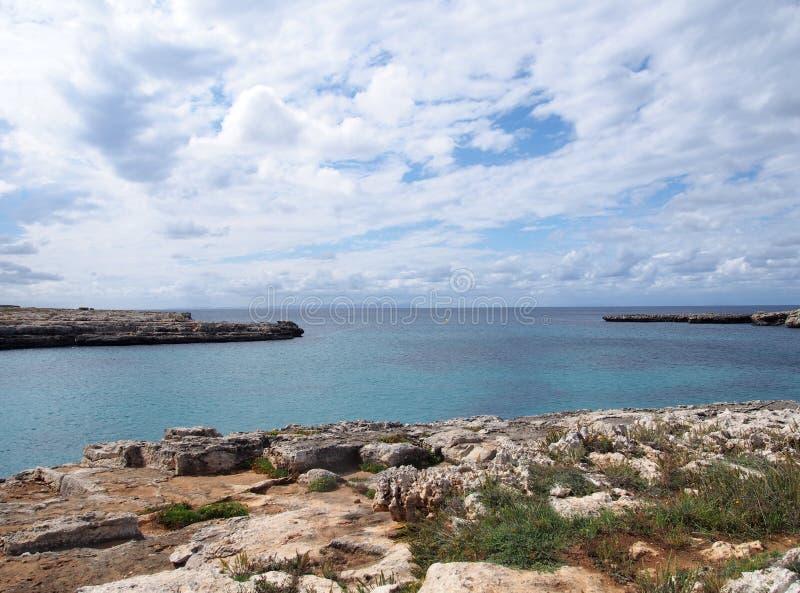 Clifftop-Ansicht der Bucht an cale santandria im menorca mit felsigem Ufer und im blauen Sommermeer mit weißen Wolken lizenzfreie stockfotografie