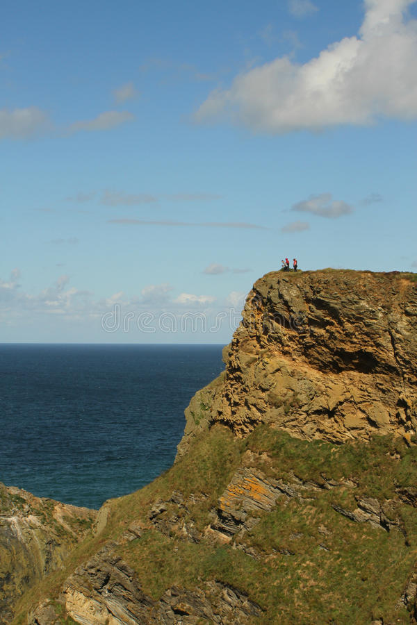 Clifftop dangerous view. Walkers marvel at the drop from the clifftop view at Hell's Mouth, Cornwall stock photo