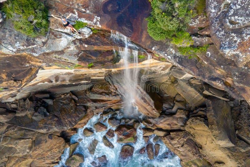 Clifftop-Frau, die durch den Rand des Wasserfalls stolpernd in Ozean sitzt stockfoto