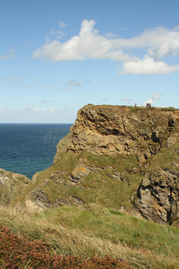 Clifftop view. Walkers enjoying the blue sky and turquoise sea from a clifftop view at Hell's Mouth, Cornwall stock photo