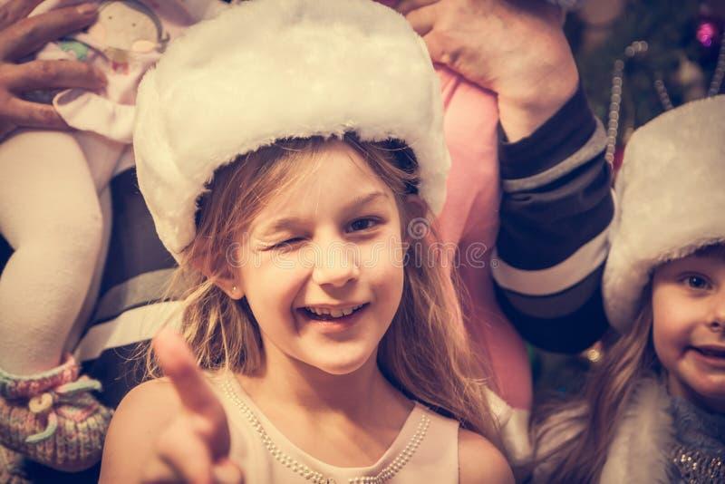 Cligner de l'oeil l'enfant regardant l'appareil-photo avec le geste d'approbation pendant des vacances de Noël image stock