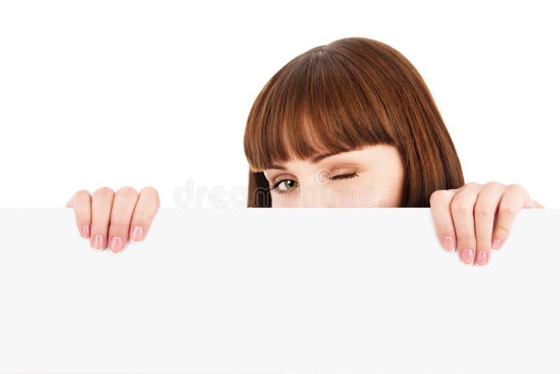 Cligner de l'oeil le femme jetant un coup d'oeil au-dessus du panneau-réclame blanc photographie stock
