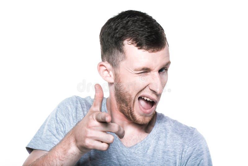 Cligner de l'oeil le jeune homme indiquant son doigt vous image libre de droits
