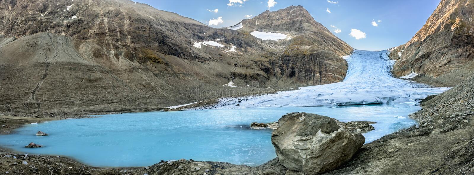 Climate change banner - panorama view of melting glacier. And three people climbing in the background. Steindalsbreen glacier - Norway royalty free stock photography