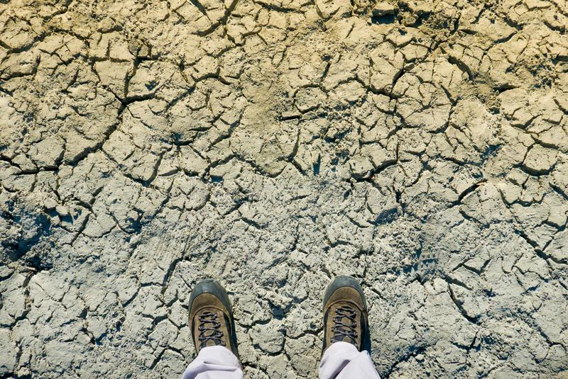 Climate change concept, man in dirty shoes stands on dried crack royalty free illustration