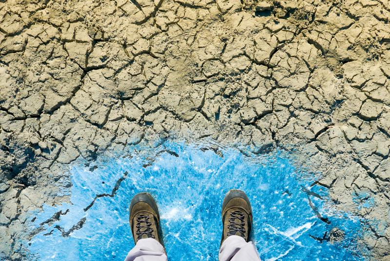 Climate change concept, man in dirty shoes stands on ice surface stock illustration