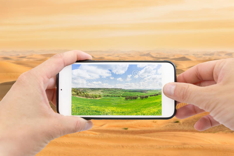 Climate change with desertification process. Smartphone photographing a field, desert in the background stock photo
