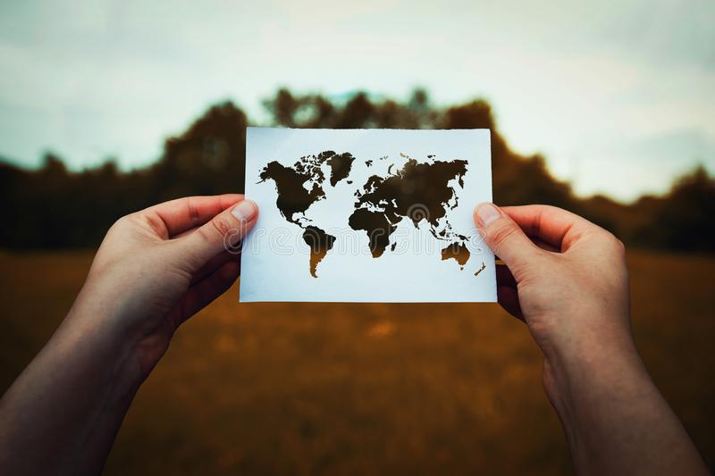 Climate change global issue. Climate change problem, destruction of nature concept. Human hands holding a paper sheet with world map icon over a dry grass field royalty free stock photos