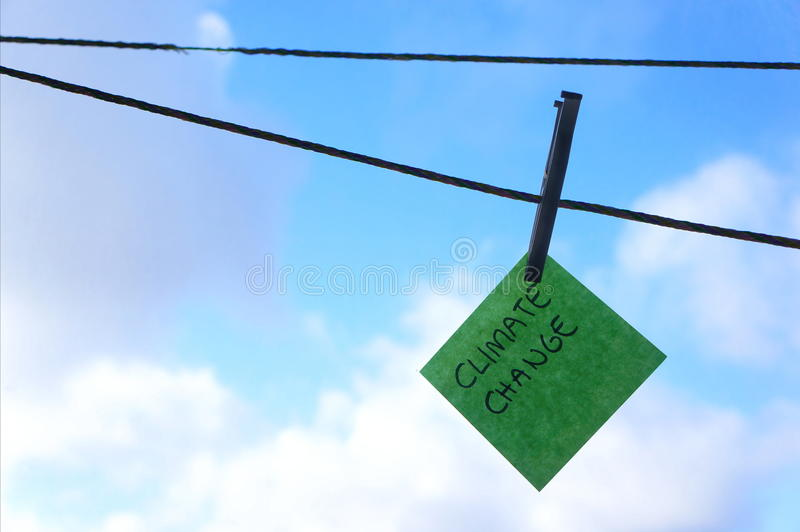 Climate change, global warming concept, post it note, washing line. Post it note on washing line hanging on a washing line in beautiful wather with a blue sky royalty free stock photography