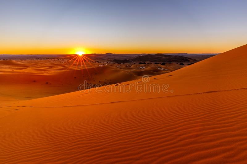 Climate Change, global warming and desertification concept. Sunrise in the sand dunes of Erg Chebbi near Merzouga.A large of dunes formed by wind-blown sand just stock photos