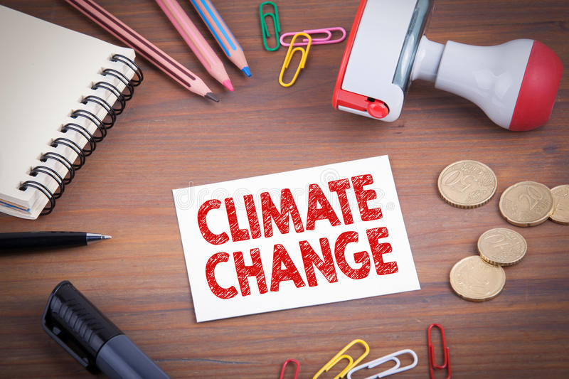 Climate Change. Wooden office desk with stationery, money and a note pad.  stock image