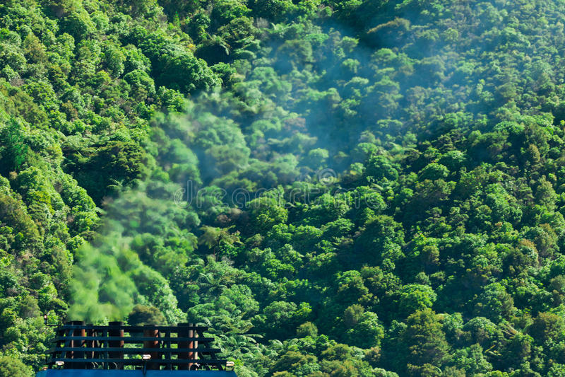 Climate gas pollution concept, smoke and forest. Greenhouse gas atmospheric pollution concept of blue smoke discharged from chimney in front of lush green royalty free stock image