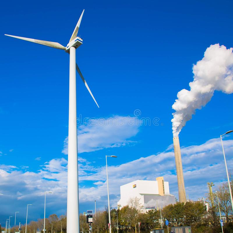 Climate problems. An electric windmill and factory chimney. Climate problems. An electric windmill and a factory chimney with smoke against the blue sky royalty free stock photo