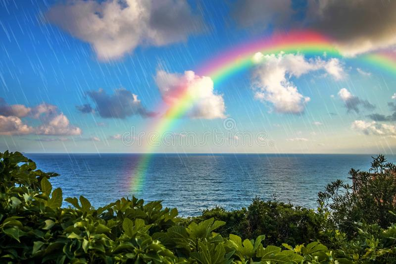 Climate and weather changes concept with rain and rainbow. royalty free stock image