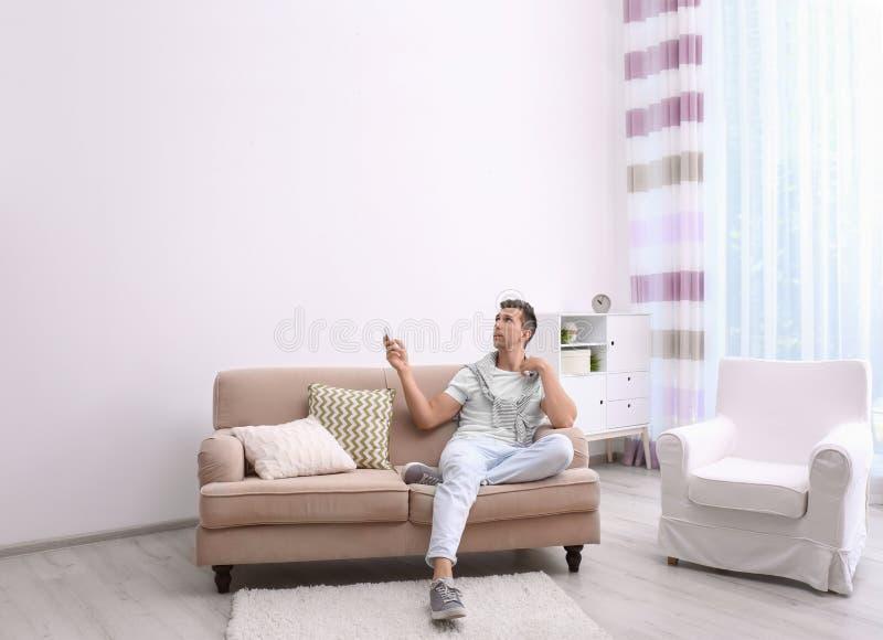 Climatiseur fonctionnant de jeune homme avec à télécommande image libre de droits