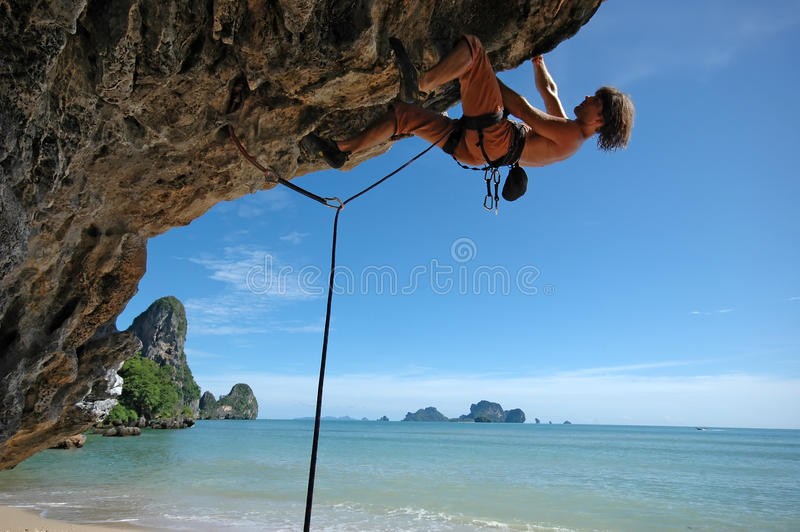 Climb on!. Adult climbing hard overhanging wall in Krabi, Thailand royalty free stock images