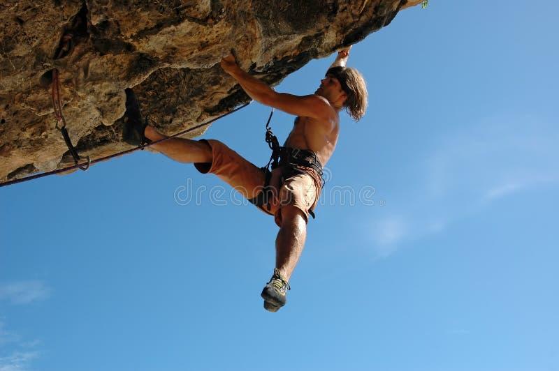 Climb on!. Adult climbing hard overhanging rock royalty free stock photos