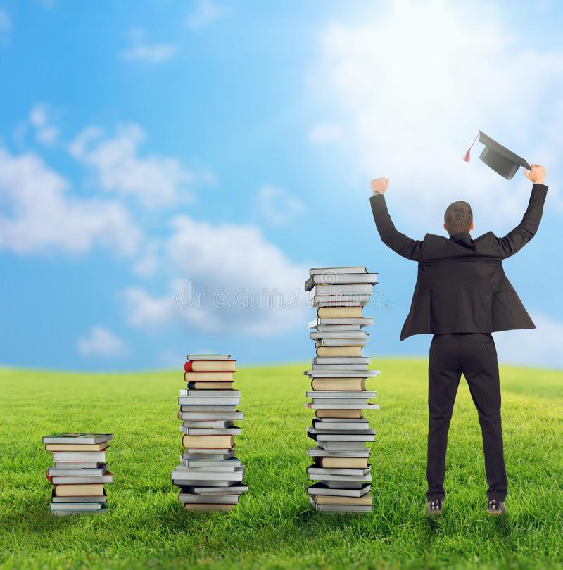 Climb to the degree and the job. Businessman sitting on a pile of books with graduation cap royalty free stock images
