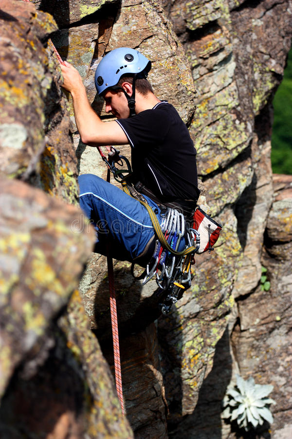 A climber. Rappelling with equipment between rocky cliff mountain stock images