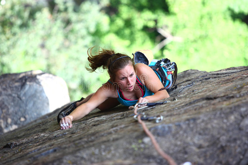 Climber. A female climber climbing a rocky cliff in the forrest stock photo
