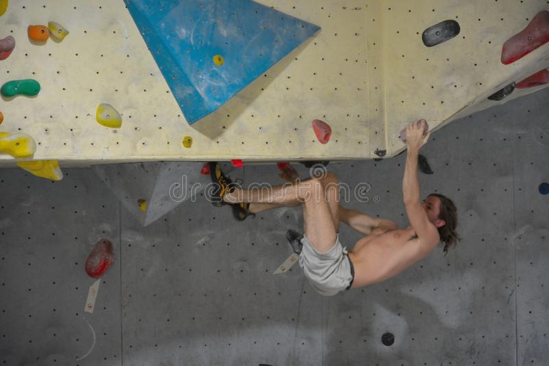 Climber in action, hanging up side down. MORTSEL, BELGIUM, 6 OCTOBER 2014: Unidentifiable Climber in action, hanging up side down, Climber trying to reach the royalty free stock image