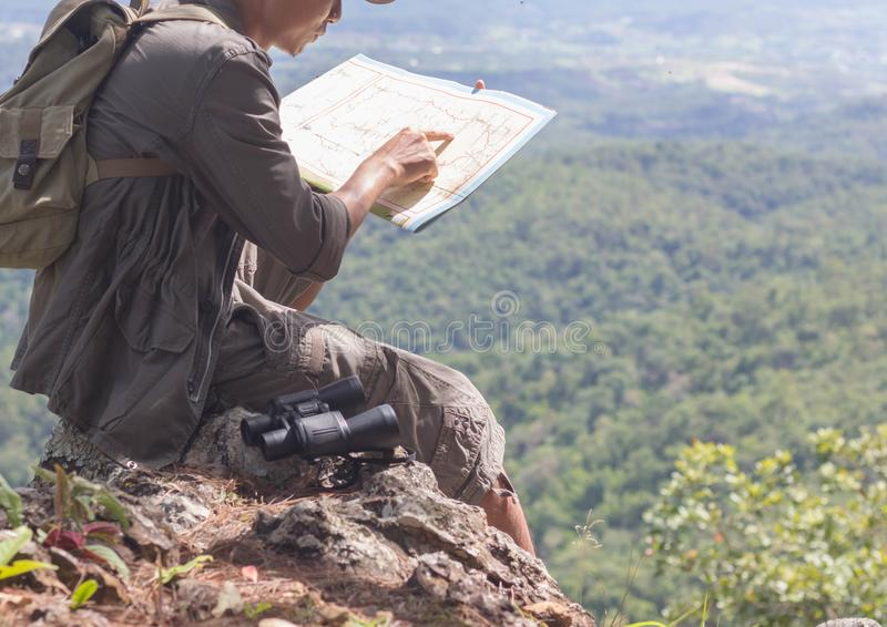 A climber with a backpack sitting looking at the map in the mountains stock photos