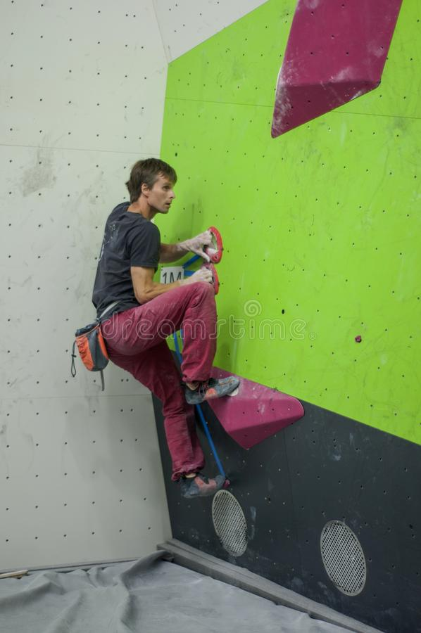 Climber in a boulder gym. Man climbing bouldering problem. Colorful volumes and holds on black and green wall. Climbing man. Climber in a boulder gym. Man royalty free stock images