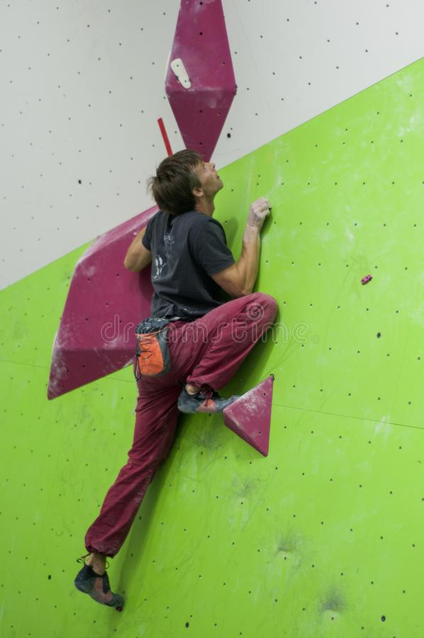Climber in a boulder gym. Man climbing bouldering problem. Colorful volumes and holds on white and green wall. Climbing man. Climber in a boulder gym. Man stock images