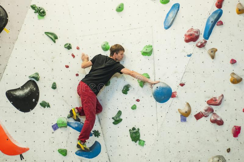 Climber in a boulder gym. Man climbing bouldering problem. Colorful volumes and holds on a white wall. stock photography