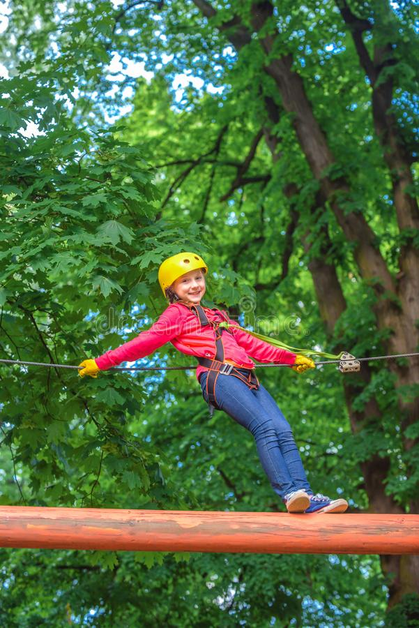 Climber child on training. Child climbing on high rope park. Cargo net climbing and hanging log. Children fun. Portrait royalty free stock photo