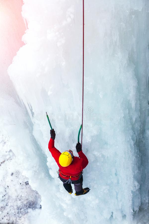 The climber climbs on ice. A young climber climbs on ice climbing and winter sport activities in cold weather stock photography